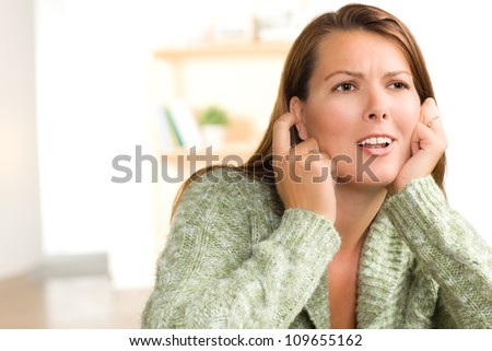 Beautiful white female at home wearing a green sweater with straight long brunette hair.