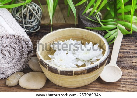 Beautiful White Flowers in the Water in a Bamboo Bowl.Spa and Wellness Concept - stock photo