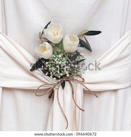 Beautiful white flowers. Tulips and gypsophila. Arrangement in draped fabric. - stock photo