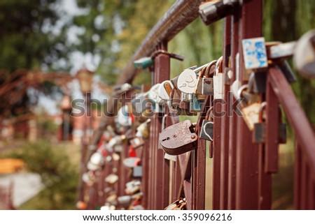 Beautiful white heart-shaped padlock locked on iron chain, romance concept - stock photo