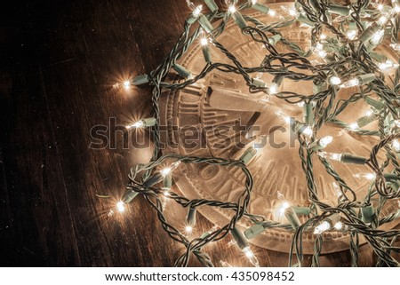 Beautiful white holiday lights set on a dark wooden floor and a vintage time dial for the Kwanzaa and Christmas holiday season