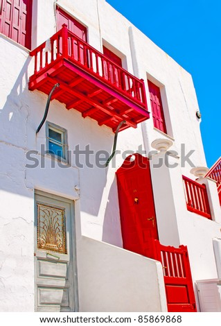 Beautiful white house with red colored windows in Mykonos island in Greece