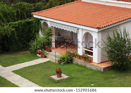 Beautiful white house with red tile roof, small terrace and lawn in the garden.  - stock photo