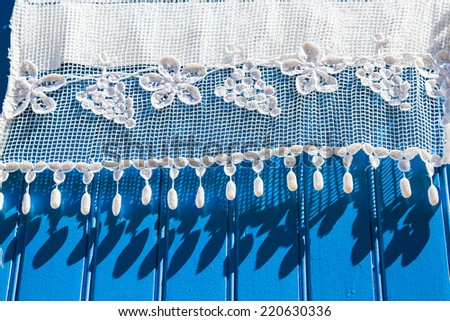 beautiful white lace curtains on a blue wooden shutter - stock photo