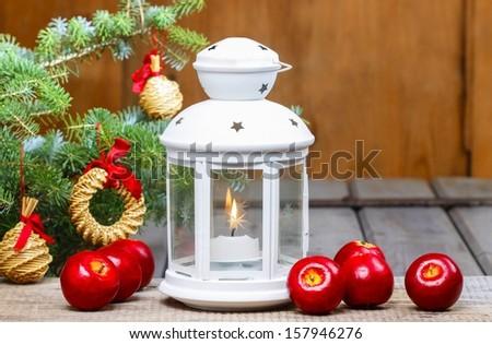 Beautiful white lantern on wooden table, red apples around - stock photo