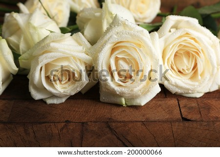 Beautiful white roses on wooden table