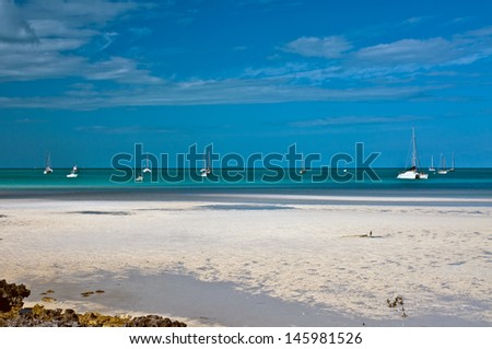 Beautiful white sand beach with small tidal pools at low tide, surrounded by crystal clear turquoise waters with many sailboats anchored in the background.  islands of the bahamas - stock photo