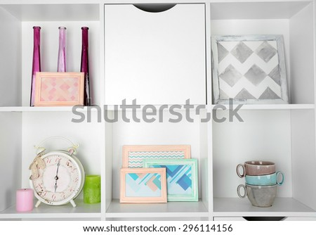 Beautiful white shelves with different home objects - stock photo