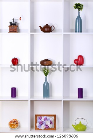 Beautiful white shelves with different home related objects - stock photo