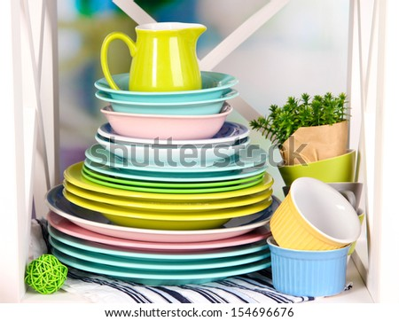 Beautiful white shelves with tableware and decor, on bright background, close-up - stock photo