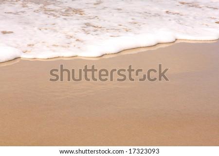 Beautiful white surf washing up on the beach - stock photo