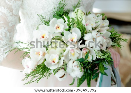Beautiful white wedding bouquet in hands of the bride
