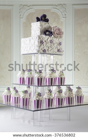 Beautiful white wedding cake with floral decoration - stock photo