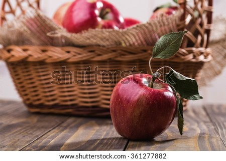 Beautiful whole ripe juicy red apple with green leaves on stalk in front of basket full of apples decorated with burlap on wooden table on white wall background, horizontal photo - stock photo