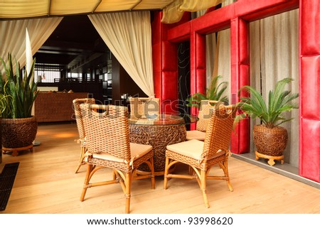 Beautiful wicker chairs and table in empty classy restaurant