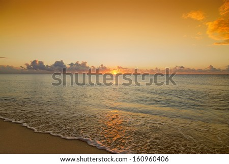 Beautiful wide angle shot of a sunset or sunrise over caribbean sea. Low perspective view. - stock photo