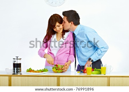 Beautiful wife is preparing some food for lunch and her husband is kissing her in her cheek - stock photo