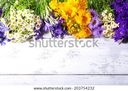 Beautiful wild flowers on wooden background - stock photo