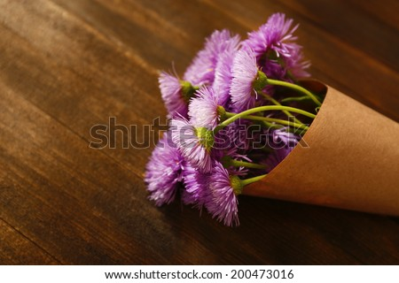 Beautiful wild flowers on wooden table - stock photo