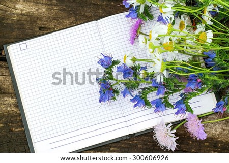 Beautiful wildflowers and a notebook to record with free space for text. Good for holiday greetings - stock photo