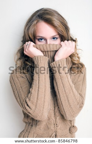 Beautiful winter fashion girl playing with her turtleneck sweater. - stock photo