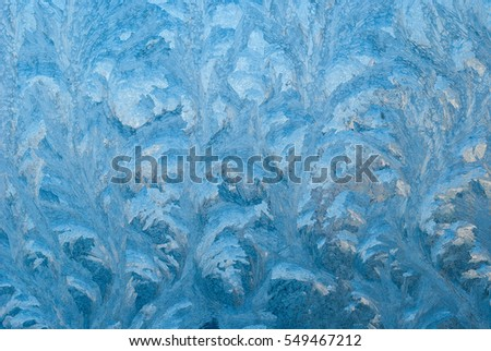 Beautiful winter frost and the curls of ice on glass. This is frosty pattern on glass winter window. Ice Patterns On A Winter Window,Close Up. Frosty pattern at a winter window glass