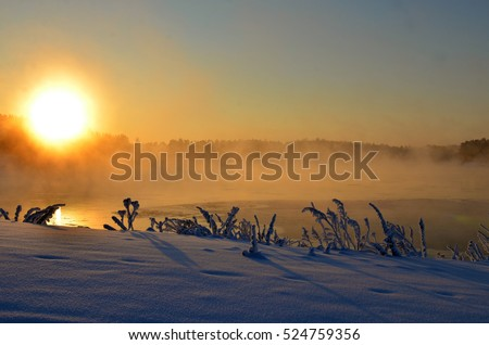 Beautiful winter frosty landscape. the sun breaks through the mist over the water. on the shore of a small village. backlight. beautiful screensaver for your desktop