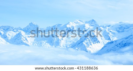 beautiful winter landscape of Caucasus mountains with clouds and blue sky, panorama