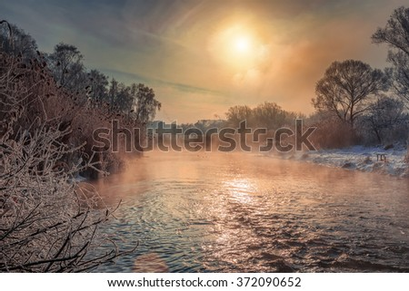 beautiful winter landscape. the morning sun sparkling on the waves of a small river. covered by fog. The beauty of the world. Europe. Ukraine. Ternopil - stock photo