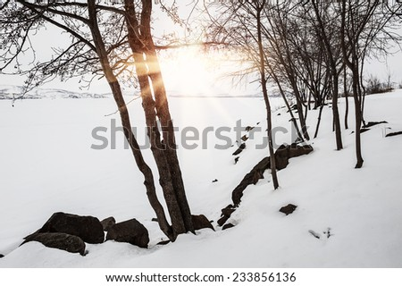 Beautiful winter landscape with snow-covered lake at sunset - stock photo