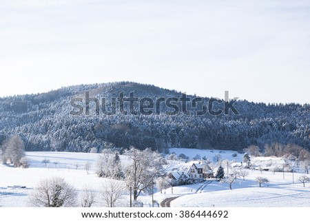 Beautiful winter landscape with snow covered trees and mountains and lonely road in small village  - stock photo