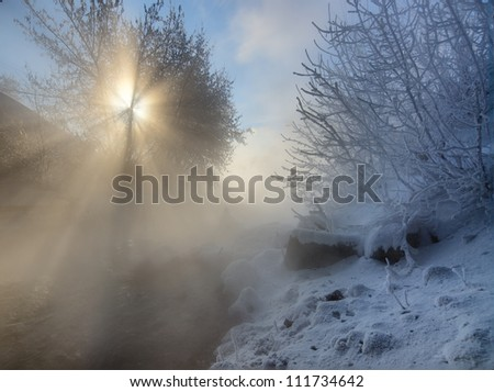 Beautiful winter landscape with visible sun-rays and frozen river - stock photo