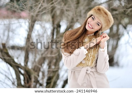 Beautiful winter portrait of young smiling woman outdoor - stock photo