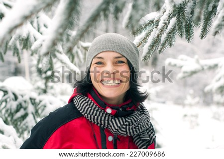 Beautiful winter portrait of young woman in the winter snowy scenery - stock photo