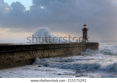 Beautiful winter seascape at sunset  with big waves over pier and lighthouse, Porto, Portugal - stock photo