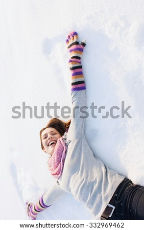 Beautiful winter woman have fun in winter park lying on snow - stock photo