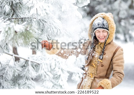 Beautiful winter woman have fun in winter park lying on snow. copy space - stock photo