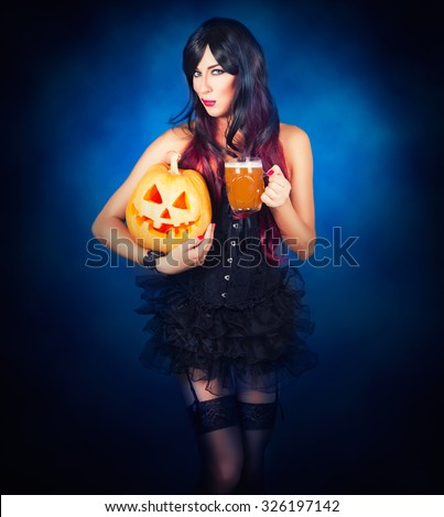 Beautiful witch in black gothic Halloween costume holding Jack-o-lantern in hands and beer - stock photo