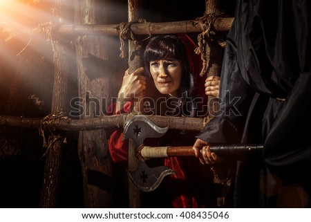 Beautiful witch in red dress in the dungeon is looking on the sun ray. - stock photo