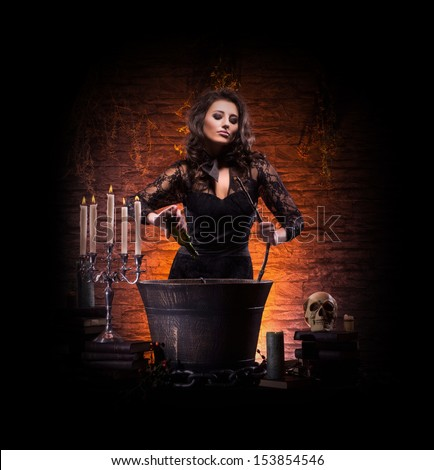 Beautiful witch making the witchcraft isolated on black. Halloween image. - stock photo