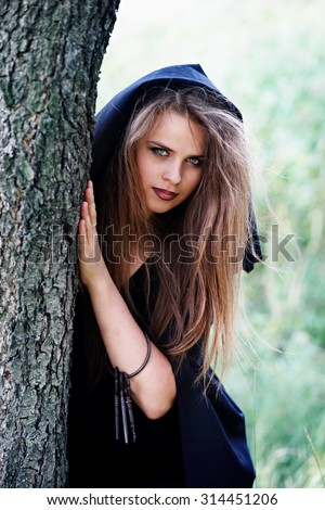 Beautiful witch with keys peeking from behind a tree - stock photo