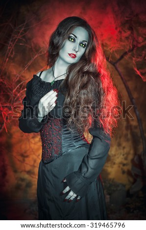 Beautiful witch with long hair on Halloween background - stock photo