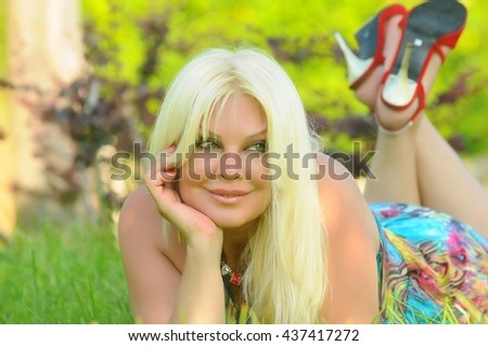 Beautiful with nice smile blonde young women in green grass in the summer park. Girl with magic green eyes.  - stock photo