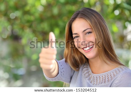 Beautiful woman agreement with thumb up outdoor with a green unfocused background                - stock photo