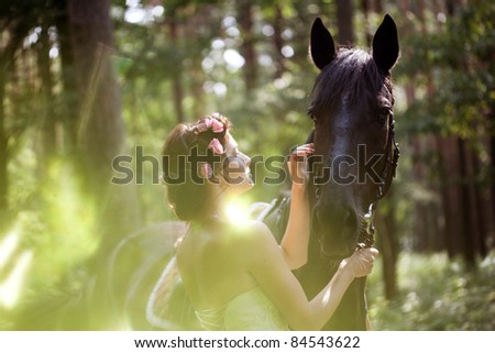 Beautiful woman and a dark horse - stock photo