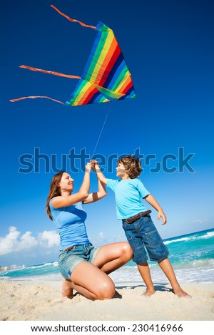 Beautiful woman and boy holding arms and flying kite in the sky during sunny day on beach coast and ocean waves