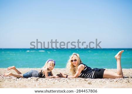Beautiful woman and her charming daughter resting on the beach  - stock photo
