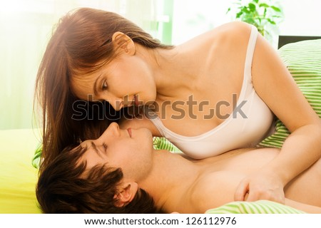 Beautiful woman and her husband playing in the bed - stock photo