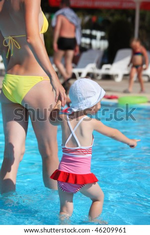 beautiful woman and little girl going on paddling pool in aquapark - stock photo