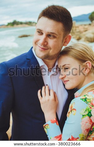 beautiful woman and stylish groom on rocks, on the background of a sea,